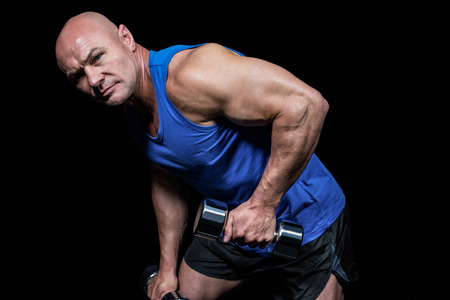 shaved head: Portrait of fit man exercising with dumbbells against black background