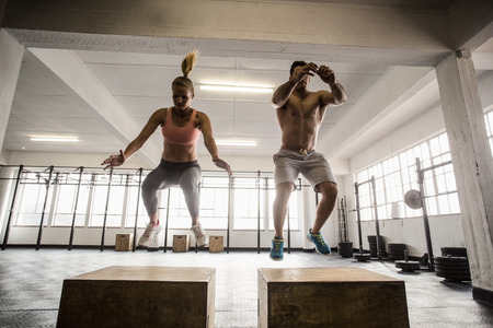 men exercising: Fit couple doing set of box jumps in crossfit gym