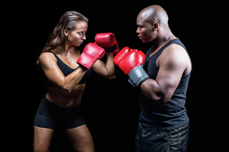 fighting stance: Male and female boxer with fighting stance against black background