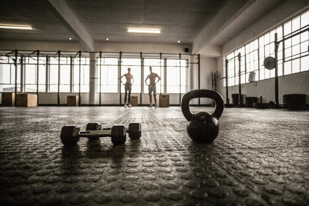 lean out: Two fit people on the background in crossfit gym Stock Photo