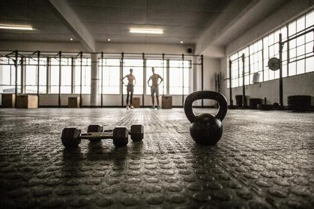 Zwei fit Menschen auf dem Hintergrund in CrossFit Fitness-Studio