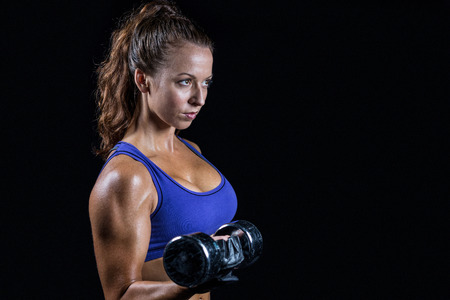 free weight: Side view of fit woman lifting dumbbell against black background Stock Photo