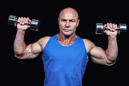 free weight: Portrait of man lifting dumbbells with arms raised against black background