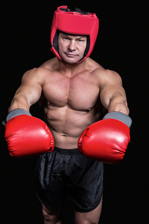 pokrývka hlavy: Portrait of boxer with red gloves and headgear against black background