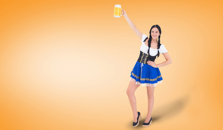 tankard: Pretty oktoberfest girl holding beer tankard against orange vignette Foto de archivo