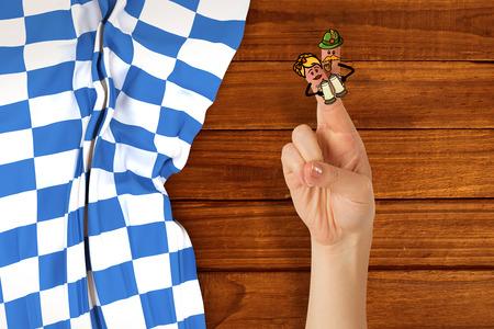 checker flag: Oktoberfest character fingers against overhead of wooden planks Stock Photo