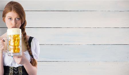 tankard: Oktoberfest girl drinking jug of beer against painted blue wooden planks