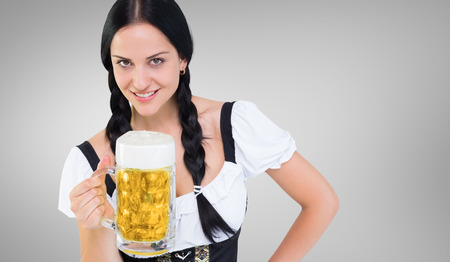 tankard: Pretty oktoberfest girl holding beer tankard against grey vignette Foto de archivo