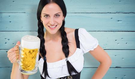 tankard: Pretty oktoberfest girl holding beer tankard against painted blue wooden planks