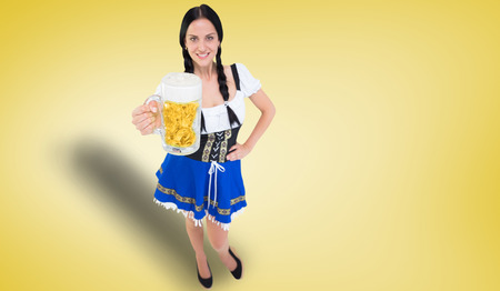 tankard: Pretty oktoberfest girl holding beer tankard against yellow vignette Foto de archivo