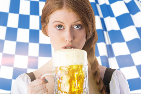 tankard: Oktoberfest girl drinking jug of beer against blue and white flag