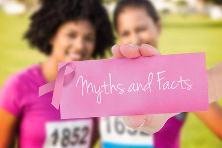 brasiere: La palabra mitos y hechos y mujer joven que sostiene la tarjeta en blanco contra dos corredores sonrientes apoyo del marat�n del c�ncer de mama