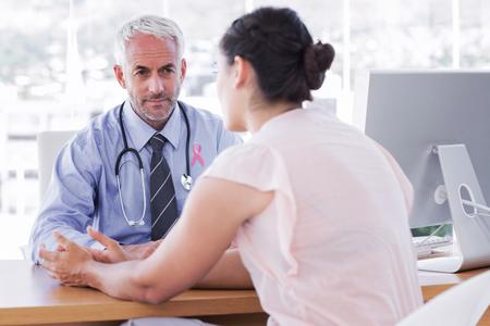 cancer de mama: conciencia cinta rosa contra el paciente explicando su dolorosa para el médico