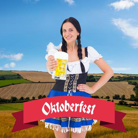 tankard: Pretty oktoberfest girl holding beer tankard against country scene