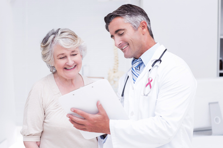 cancer de mama: conciencia cinta rosa contra el m�dico y el paciente que discuten sobre los informes
