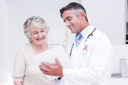 Roze voorlichtingslint tegen arts en patiënt bespreken over berichten Stockfoto