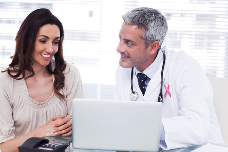 Roze voorlichtingslint tegen docter blijkt iets op de laptop aan zijn patiënt Stockfoto