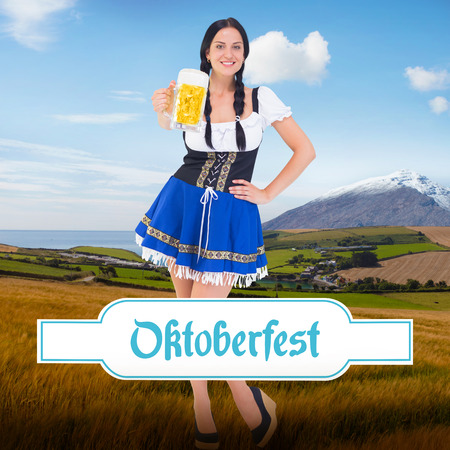 tankard: Pretty oktoberfest girl holding beer tankard against country scene with mountain