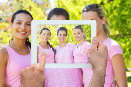 young breast: Hand holding tablet pc against smiling women in pink for breast cancer awareness