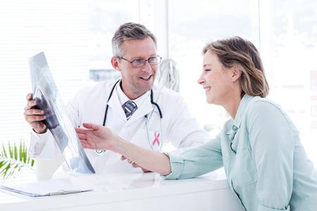 mujer desnuda sentada: conciencia cinta rosa contra el médico teniendo una conversación con su radiografía del paciente y la celebración