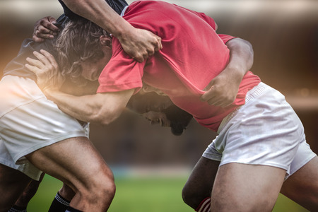 competencia: Los fans del rugbi en la arena contra jugadores de rugby haciendo un scrum