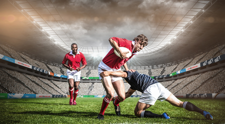Rugby stadium against rugby players tackling during game Stockfoto