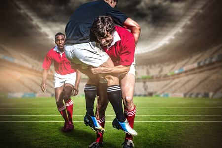 Rugby stadium against rugby players tackling during game Stok Fotoğraf