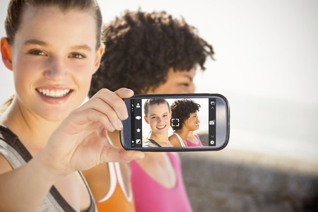 mobile phone screen: Hand holding smartphone showing against smiling sporty woman with two friends Stock Photo