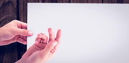 gesturing: Cropped hands gesturing against white paper over wooden wall