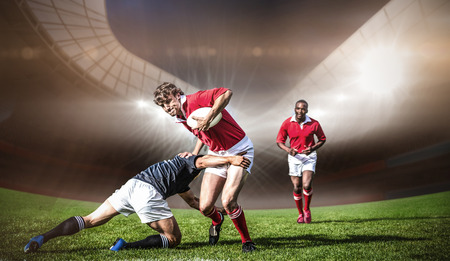 Rugby stadium against rugby players tackling during game Stock Photo