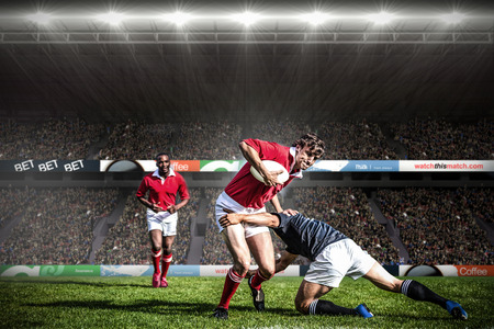 Rugby fans in arena against rugby players tackling during game Stockfoto