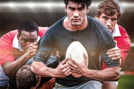 pelota rugby: Los amantes del rugby en arena contra jugadores de rugby que abordan durante el partido Foto de archivo