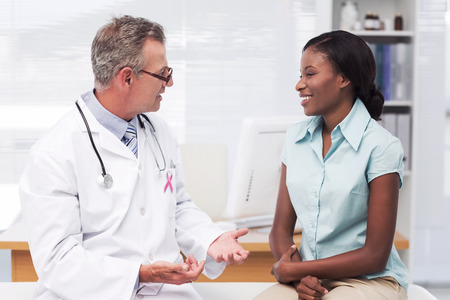 cancer symbol: Pink awareness ribbon against doctor speaking with cheerful young patient Stock Photo