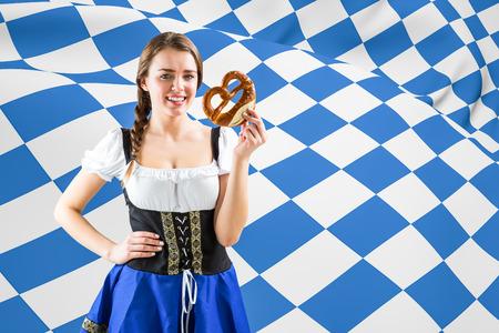 checker flag: Pretty oktoberfest girl holding pretzel against blue and white flag