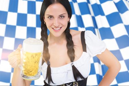 tankard: Pretty oktoberfest girl holding beer tankard against blue and white flag