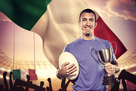 winning pitch: Portrait of smiling rugby player holding trophy and ball against rugby stadium Stock Photo