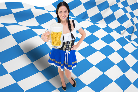 tankard: Pretty oktoberfest girl holding beer tankard against blue and white flag