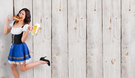 tankard: Pretty oktoberfest girl holding beer tankard and pretzel against wooden background