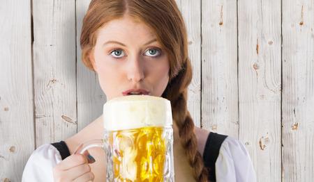 tankard: Oktoberfest girl drinking jug of beer against wooden background