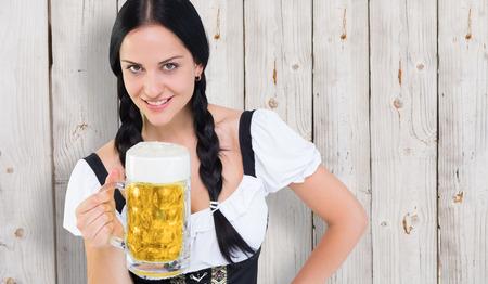 tankard: Pretty oktoberfest girl holding beer tankard against wooden background
