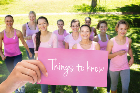 The word things to know and hand holding card against smiling women in pink for breast cancer awareness