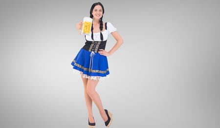 tankard: Pretty oktoberfest girl holding beer tankard against grey vignette Stock Photo