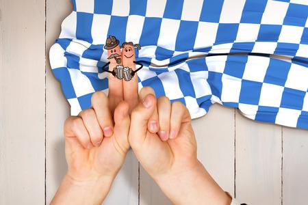 checker flag: Oktoberfest character fingers against wooden planks
