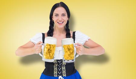 tankard: Pretty oktoberfest girl holding beer tankards against yellow vignette Stock Photo