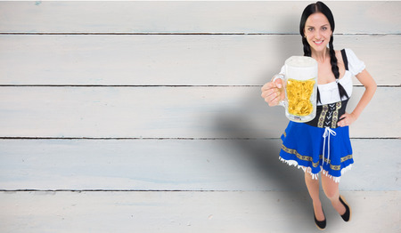 tankard: Pretty oktoberfest girl holding beer tankard against painted blue wooden planks