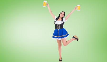 tankard: Pretty oktoberfest girl holding beer tankards against green vignette