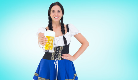 tankard: Pretty oktoberfest girl holding beer tankard against blue vignette background Foto de archivo