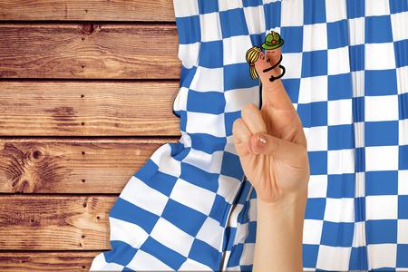 checker flag: Oktoberfest character fingers against wooden planks background