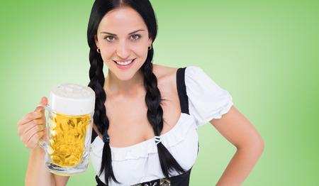 tankard: Pretty oktoberfest girl holding beer tankard against green vignette Stock Photo