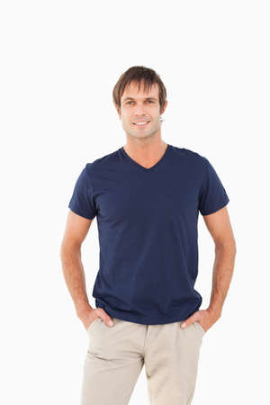 hands on pockets: Happy man standing up with his hands in his pockets against a white background LANG_EVOIMAGES
